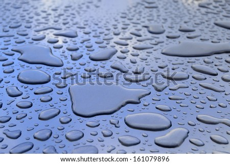 Water drops wetting a blue and metallic surface. A perspective view - stock photo