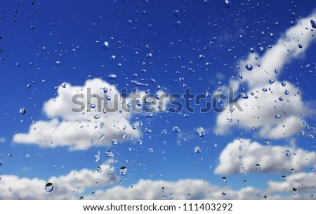 Water drops with sky and clouds on background - stock photo