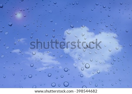 Water drops with sky and clouds on background raindrops blue  heart shaped.