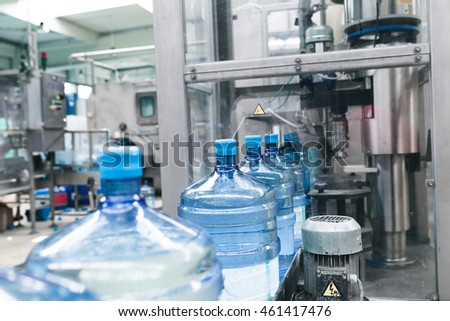 Water factory - Water bottling line for processing and bottling pure spring water into gallons. Selective focus.