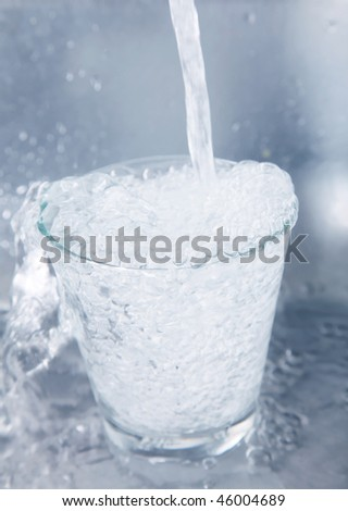 Water falling into a glass over chrome background