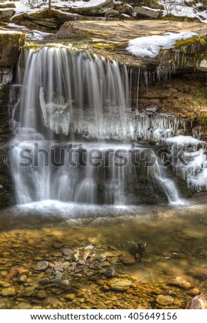 Water falls gently into a pool over partially frozen West Kill Falls in the Catskills Mountains of New York. - stock photo