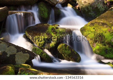 Water falls over a jumble of moss-covered boulders in Great Smoky Mountains National Park, Tennessee, USA. - stock photo