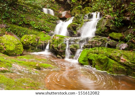 water falls over mossy rocks