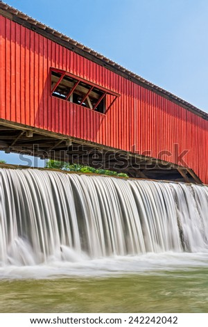 Water falls over the mill dam at the historic red covered bridge in the Parke County, Indiana town of Bridgeton.