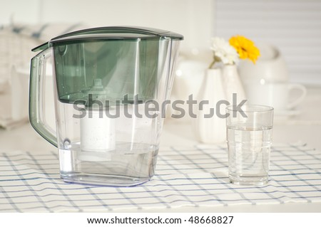 Water filter and a glass at the kitchen table - stock photo