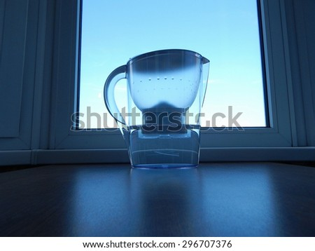 Water filter with purified water at windowsill - stock photo