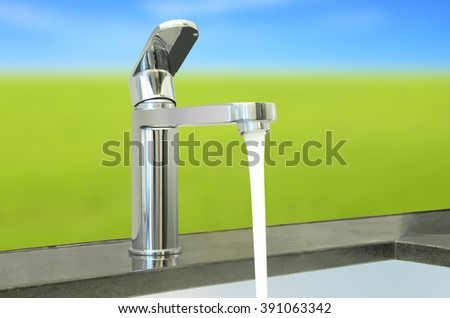 Water flow faucet granite counter on green environment. - stock photo