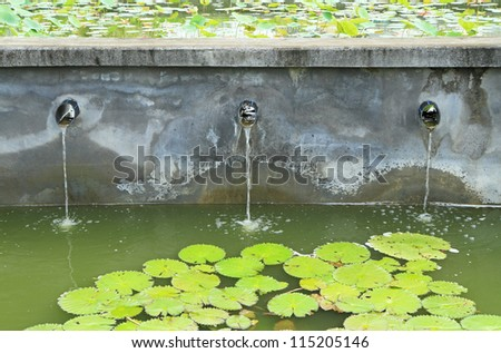 Water flow from water pipe to the lake - stock photo