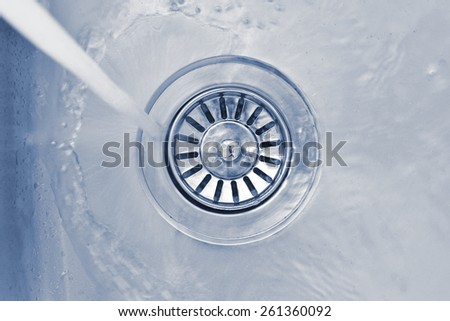 water flowing down the hole of kitchen sink - stock photo