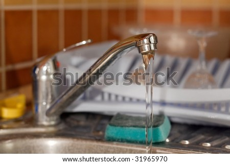 Water flowing from a kitchen tap - stock photo