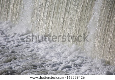 Water flowing from dam - stock photo