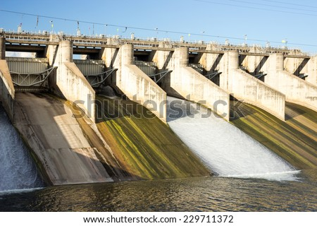 water flowing from dam gate for power and environment concept. - stock photo