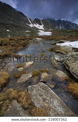 Water flowing from glacier lake,Retezat mountains, Romania - stock photo