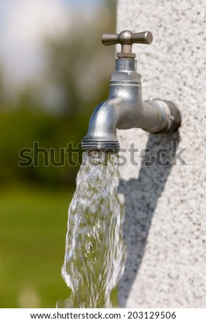 Water flowing from outdoors water tap on a sunny day. - stock photo