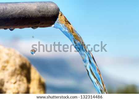 Water flowing from pipe against blurred mountain background. Shot in Hottentots-Holland Mountains nature reserve, near Somerset West, Cape Town, Western Cape, South Africa. - stock photo
