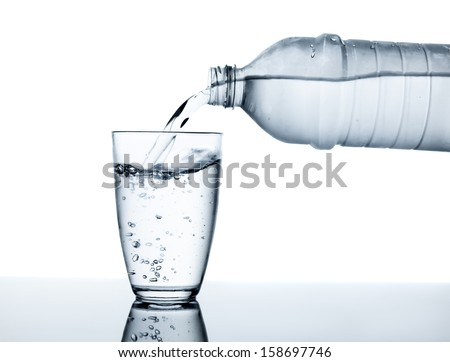 water flowing from plastic bottle into a glass - stock photo