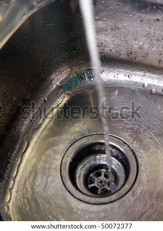 Water flowing from the faucet to the drain. - stock photo