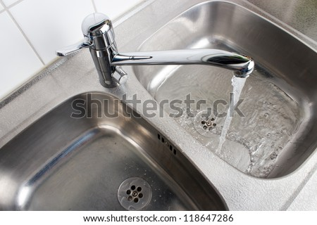 Water flowing from the faucet to the washbasin - stock photo