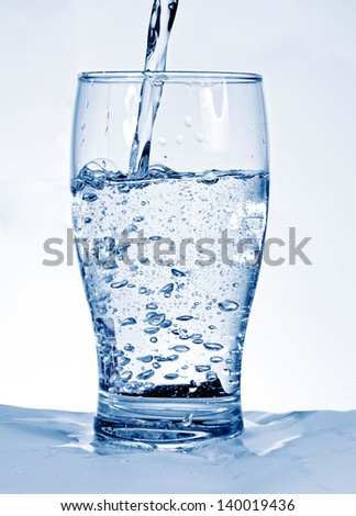 Water flowing in a glass - stock photo