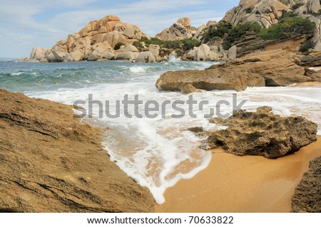 Water flowing into sandy bay - stock photo