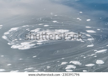 Water foam - pollution in river - stock photo
