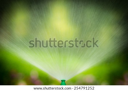 Water from sprinkler in the public park - stock photo