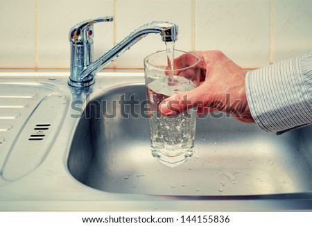 Water from the tap is poured into a glass - stock photo