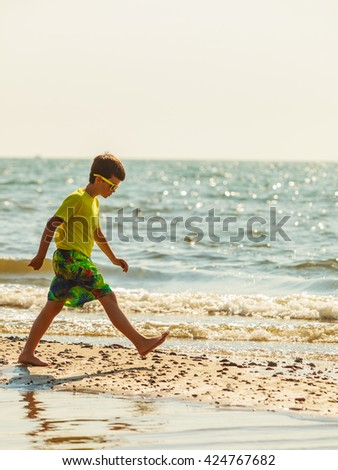 Water fun and joy outside. Little boy walking through the sea ocean. Lonely kid playing outdoors in summer clothes.
