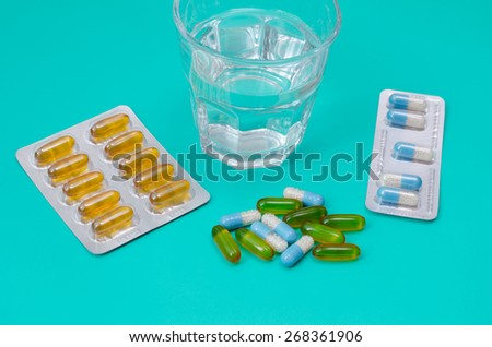 Water glass and medicaments on turquoise background - stock photo