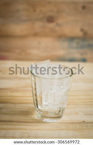 Water glass With ice cubes on wooden background - stock photo