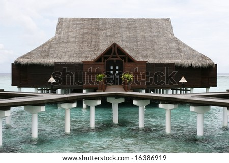 Water House With Grass Roof - stock photo