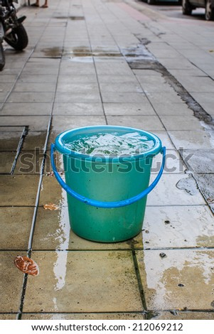 Water in plastic bucket container on sidewalk in bangkok - stock photo