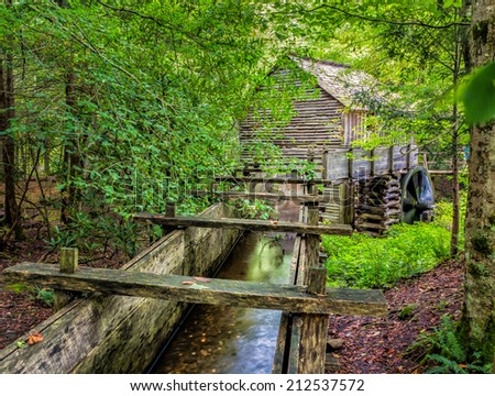 Water in trough flows to working flour mill at Cades Cove - stock photo