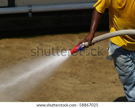 Water is directed from hose being pulled by a laborer. - stock photo