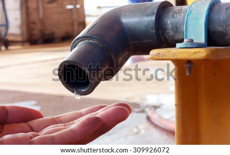 water is dropping from water tap to hand someone.  - stock photo