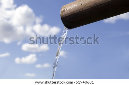 Water is falling from pipe, sky background