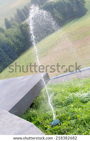 Water jet of a sprinkler head watering green grass lawn  - stock photo