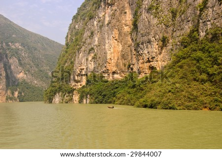 Water levels on Yangtze River are rising due to the Three Gorges Dam. A small boat is running upstream. - stock photo