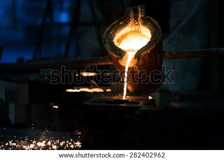 Water molten metal Being poured from the crucible Into the sand mold - stock photo
