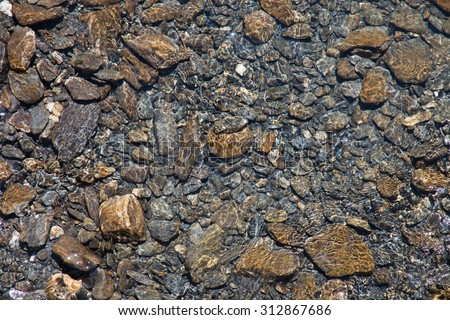 water of a mountain river flows on colorful stones viewed from above - stock photo