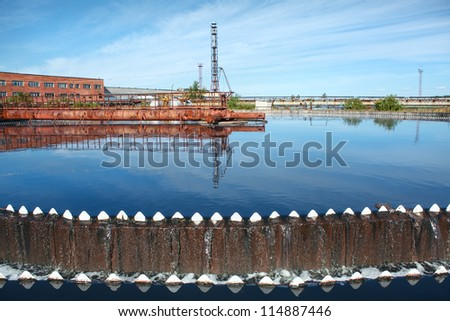 Water overflowing from circular storage tank - stock photo