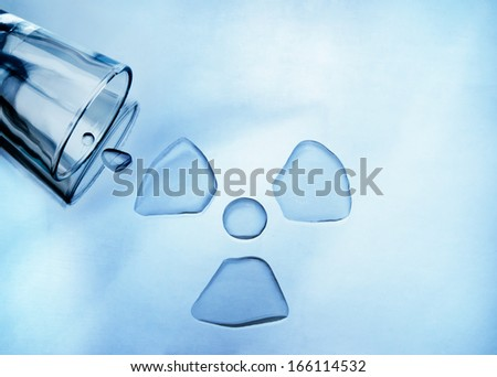 Water pollution. Glass of water spilled into shape of radioactive sign - stock photo