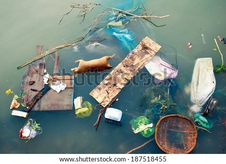 Water pollution with plastic garbage and dirty trash waste. Floating urban debris on contaminated industrial sewage litter stream.