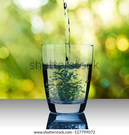 Water pour into glass on summer scene background - stock photo