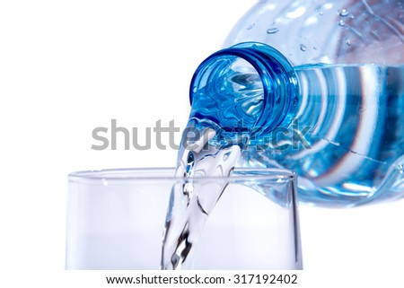 Water poured from a plastic bottle into a glass, isolated on white