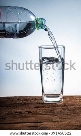Water pouring from bottle into the glass on wood