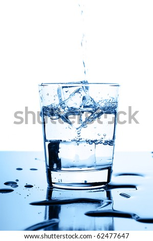 water pouring in to glass with ice cubes on glossy background - stock photo