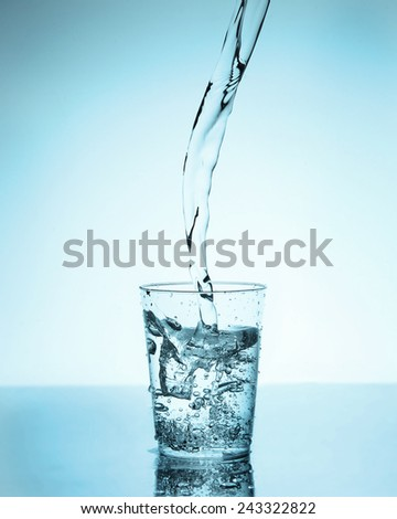 Water pouring into a glass - stock photo