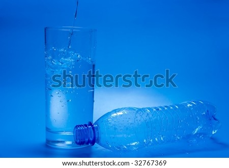 Water pouring into a glass, empty bottle next to it - stock photo